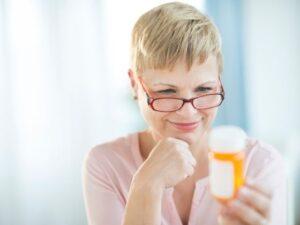 Donna con flacone vitamina D