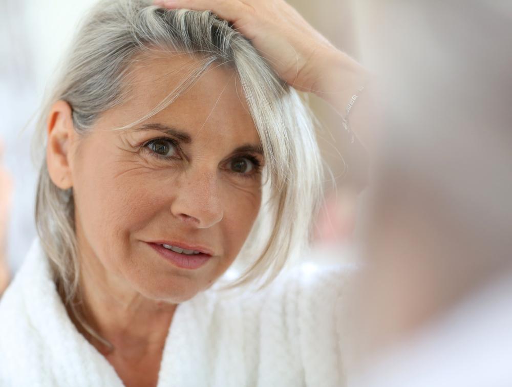 Donna con capelli grigi si guarda allo specchio