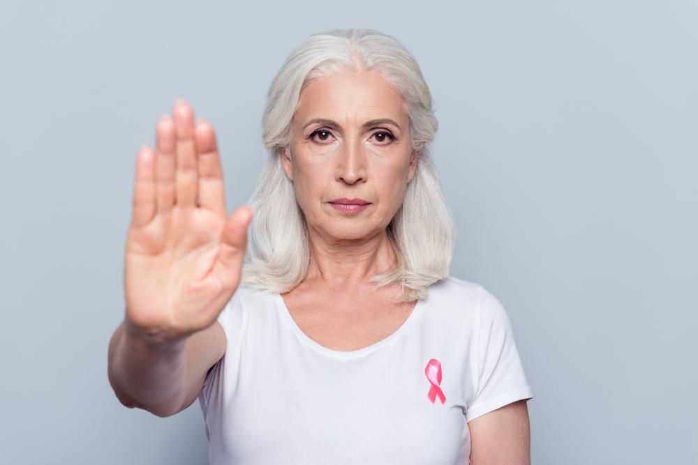 Donna con nastro rosa per tumore al seno con mano alzata in segno di stop