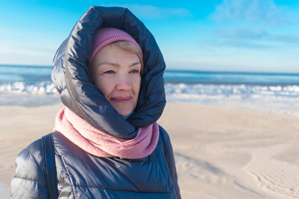 Donna protegge pelle dal freddo con sciarpa e cappello