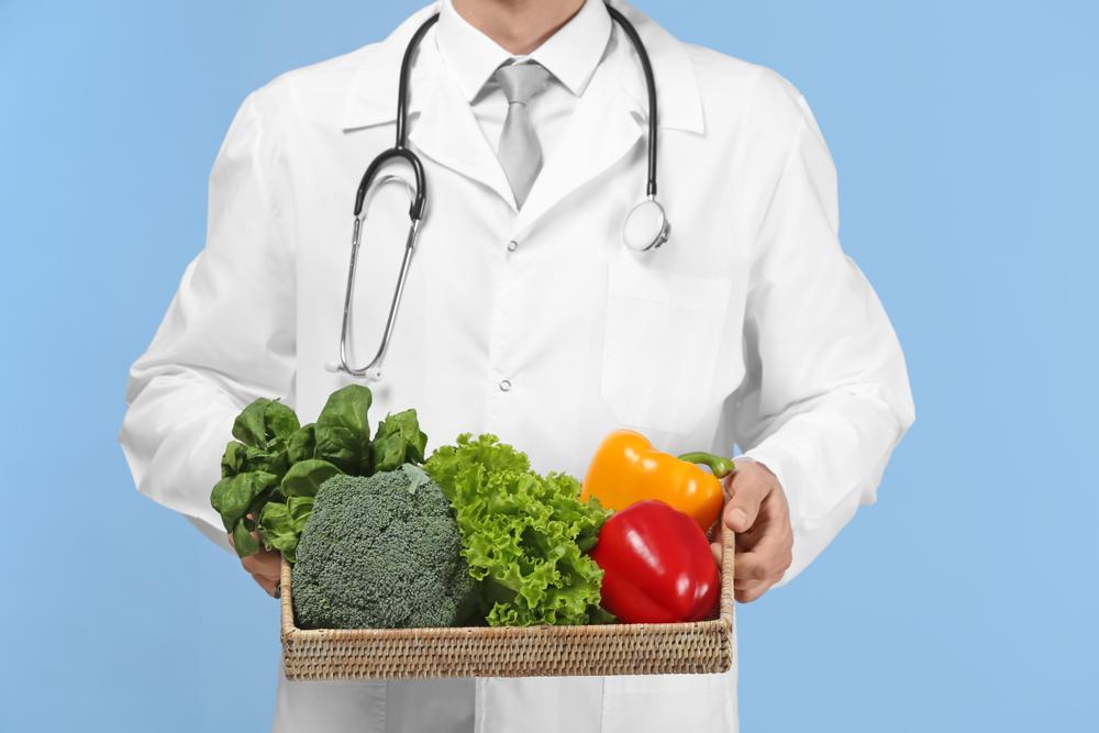 Dottore mostra verdura: esempio di consigli di alimentazione per il covid