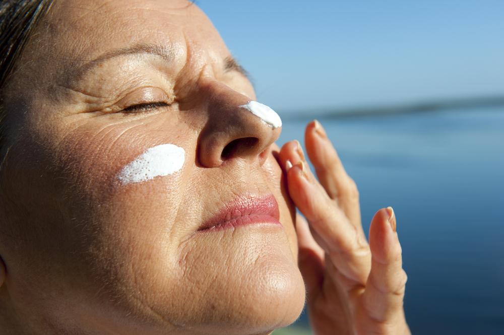 Donna prende sole con crema protettiva: esempio di effetti del sole su donne in post-menopausa
