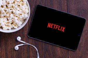 Tablet con scritta Netflix e popcorn: esempio dis erie Netflix con protagonisti senior