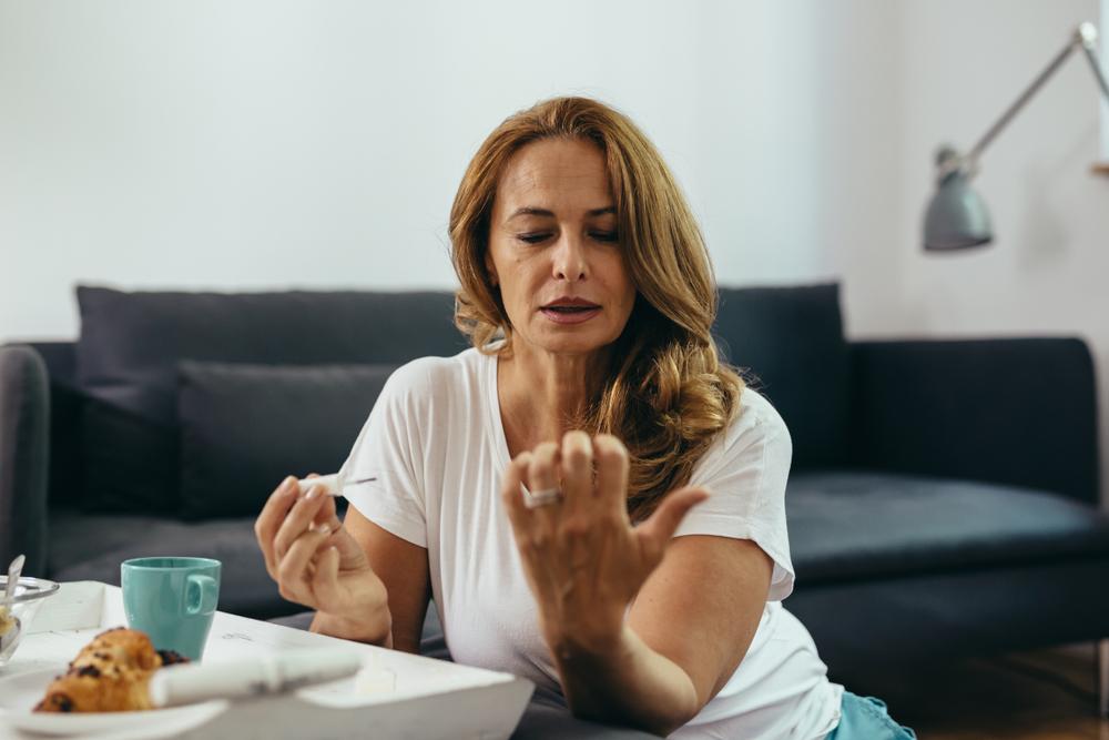 Donna si prende cura delle proprie mani mettendo lo smalto