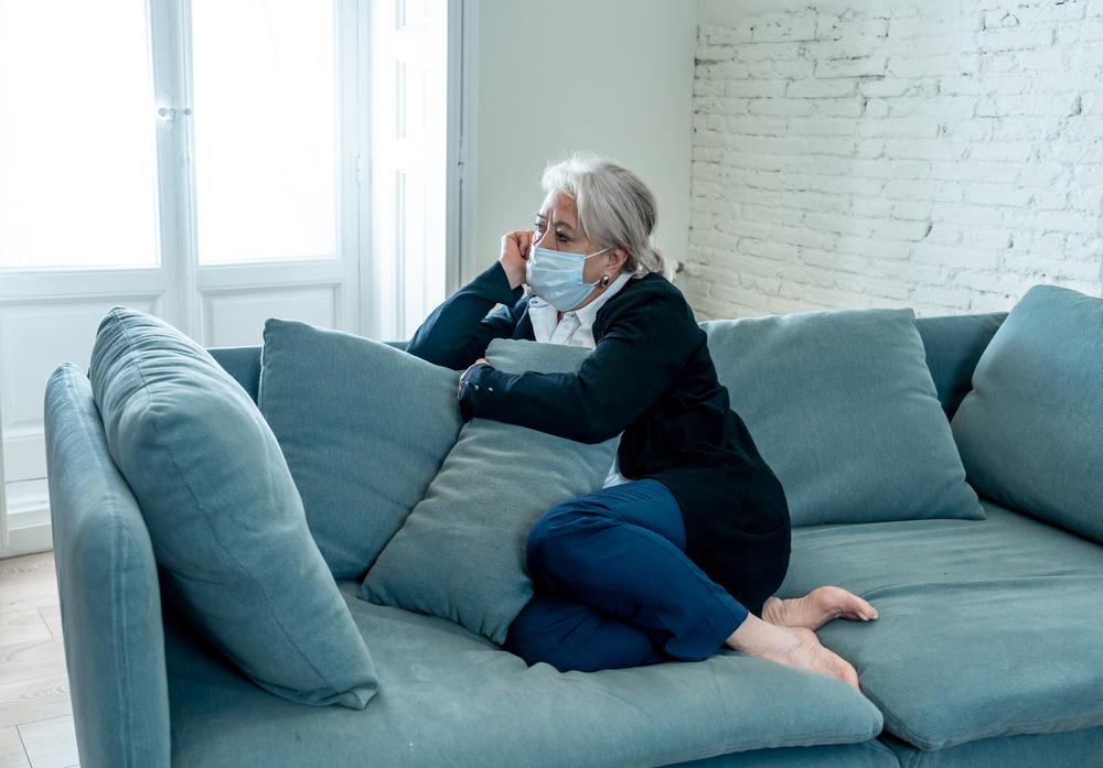 Donna depressa su divano: esempio di effetti isolamento su over 60