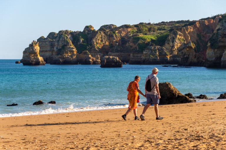 Coppia in pensione che si è trasferita all'estero cammina in spiaggia del Portogallo