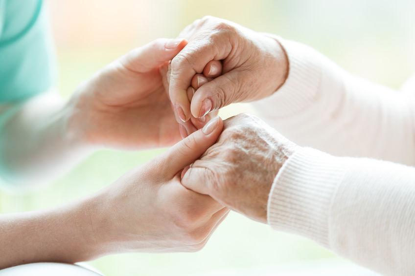 Primo piano di mani di caregiver che stringono mani anziane